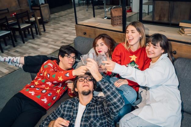 Grupo de amigos hablando sentados en un sofá en la sala de estar