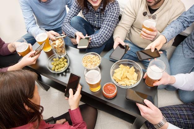 Grupo de amigos hace un aperitivo con aperitivos y cerveza en casa.