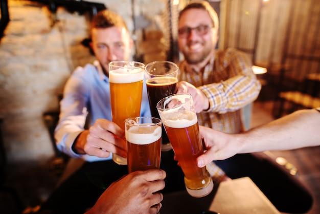 Grupo de amigos haciendo un brindis en pub.