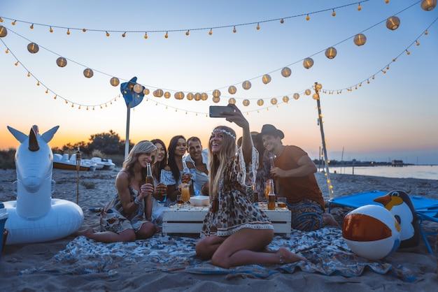 Grupo de amigos haciendo fiesta en la playa al atardecer