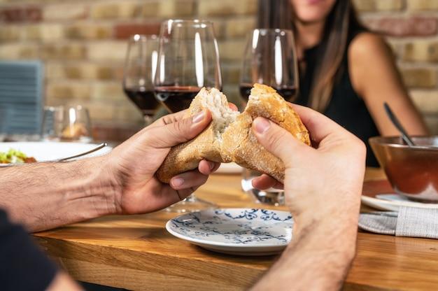 Grupo de amigos irreconocible comiendo juntos y bebiendo vino en un restaurante.