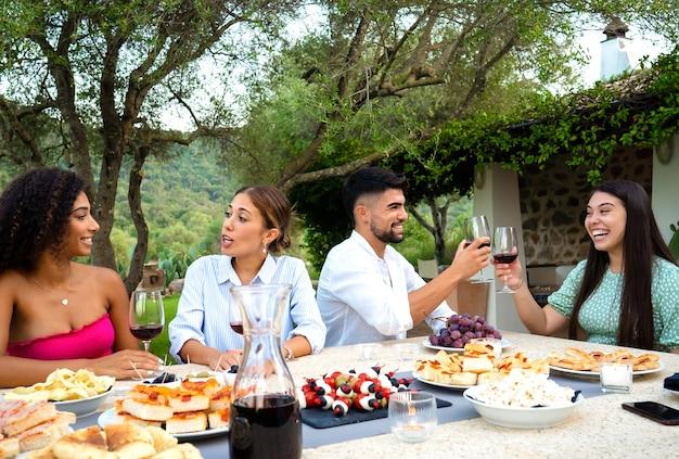 Grupo de amigos jóvenes felices multirracial brindando en el jardín al atardecer con copas de vino tinto