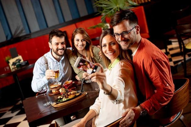 Grupo de amigos jóvenes guapos haciendo selfie con teléfono móvil y sonriendo mientras cenan en el restaurante