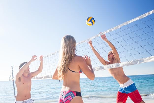 Grupo de amigos jugando al voleibol en la playa