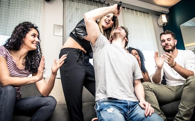 Grupo de amigos jugando duro con videojuegos y karaoke. divirtiéndose en casa
