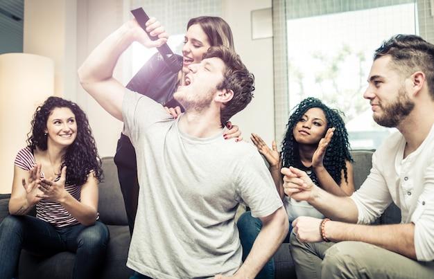Grupo de amigos jugando duro con videojuegos y karaoke