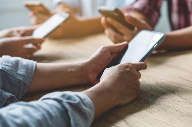 Grupo de amigos jugando juegos de aplicaciones en el teléfono móvil y en línea juntos.