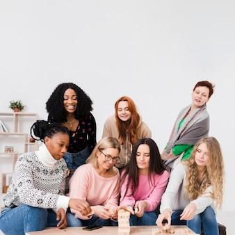 Grupo de amigos jugando juntos un juego de torre de madera
