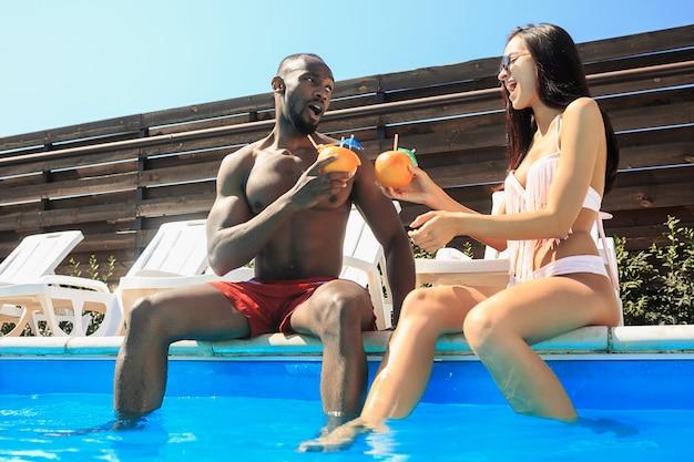 Grupo de amigos jugando y relajándose en una piscina durante las vacaciones de verano