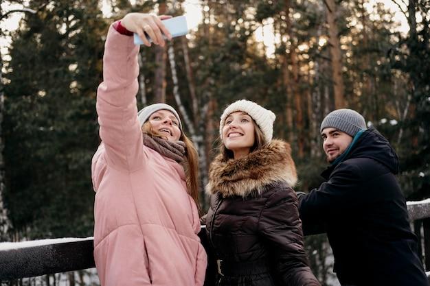 Grupo de amigos juntos tomando selfie al aire libre en invierno