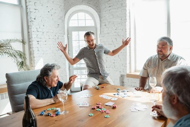Grupo de amigos maduros felices jugando a las cartas y bebiendo vino