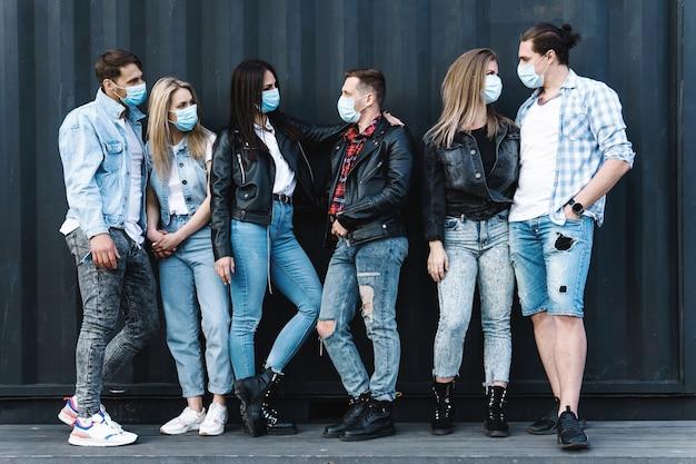 Grupo de amigos con máscaras de prevención durante una reunión en la calle