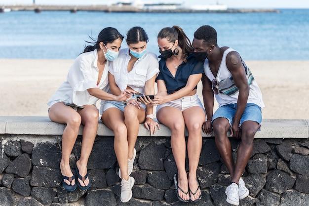 Grupo de amigos en máscaras con smartphone en la orilla del mar