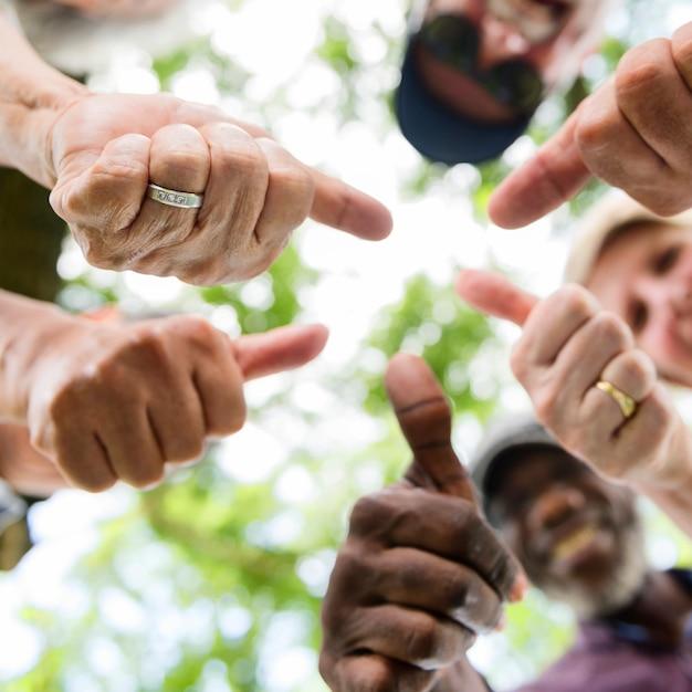 Grupo de amigos mayores al aire libre pulgares arriba concepto de positividad