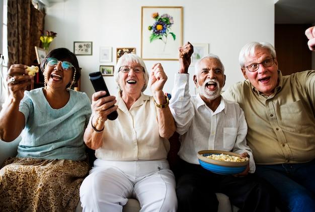Grupo de amigos mayores alegres sentados y viendo la televisión juntos