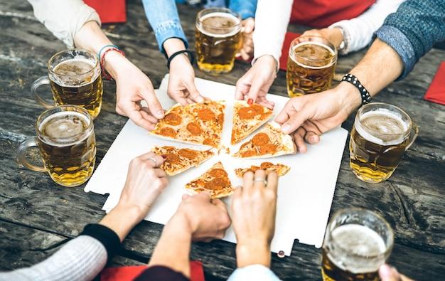 Grupo de amigos milenarios bebiendo cerveza y compartiendo rebanadas de pizza en el bar restaurante