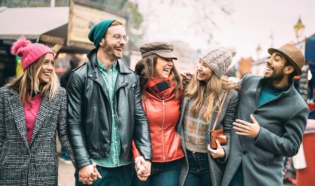 Grupo de amigos del milenio divirtiéndose juntos caminando en el centro de londres