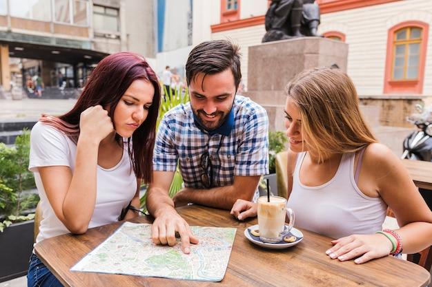 Grupo de amigos mirando el mapa en el restaurante