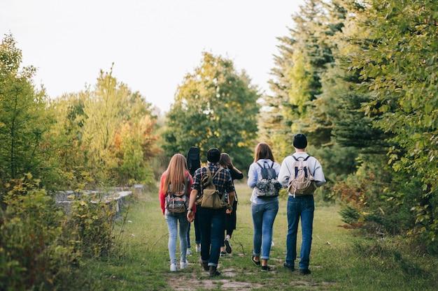 Grupo de amigos con mochilas en el bosque.