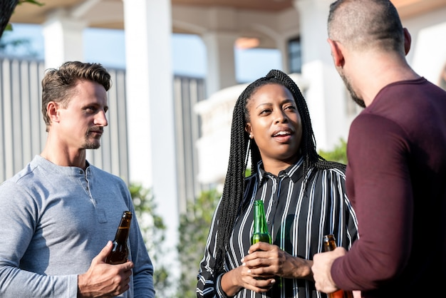 Grupo de amigos multiculturales disfrutando charlando y bebiendo alcohol.