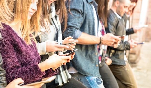 Grupo de amigos multiculturales con smartphone en el patio de la universidad universitaria
