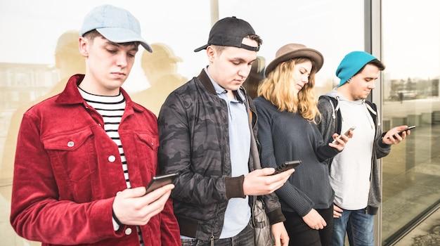 Grupo de amigos multiculturales usando un teléfono inteligente en la universidad
