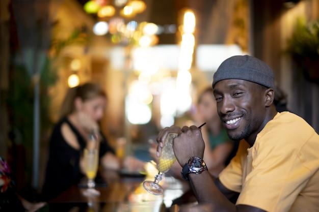 Grupo de amigos multiétnicos bebiendo cócteles y divirtiéndose en un bar