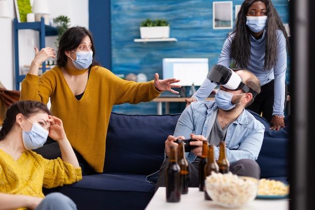 Grupo de amigos multiétnicos que se divierten jugando videojuegos experimentando la realidad virtual usando auriculares vr manteniendo el distanciamiento social en la sala de estar del hogar debido a una pandemia social.