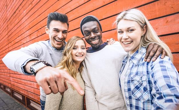 Grupo de amigos multirracial feliz que toma selfie con teléfono móvil inteligente
