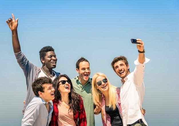 Grupo de amigos multirraciales que toman selfie en vacaciones de verano