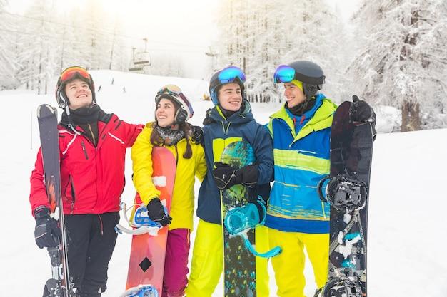Grupo de amigos en la nieve con esquí y snowboard.