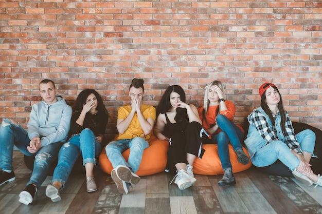 Grupo de amigos o colegas sentados en bolsas de frijoles. estilo de vida millennial
