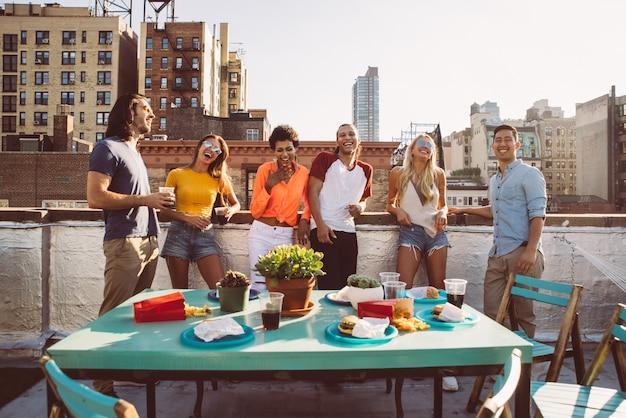 Grupo de amigos pasando el tiempo juntos en una azotea en la ciudad de nueva york, concepto de estilo de vida con gente feliz