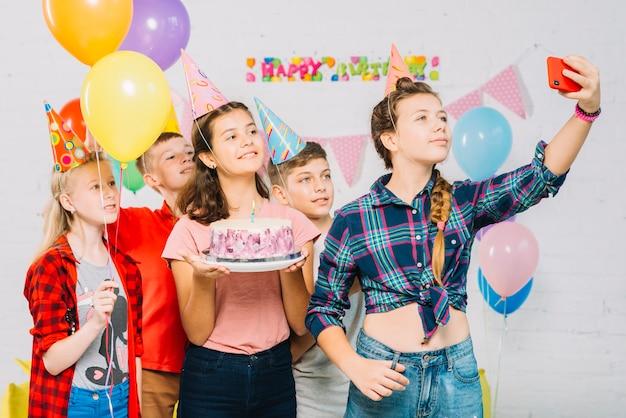 Grupo de amigos con pastel de cumpleaños tomando selfie en celular
