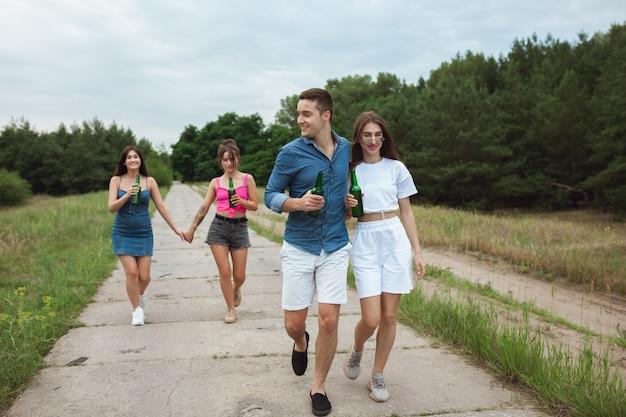 Grupo de amigos durante el picnic en el bosque de verano