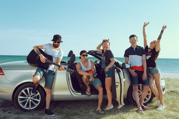 Grupo de amigos de pie en coche