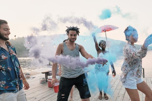 Grupo de amigos de pie en un muelle y bailando visitan el festival de colores