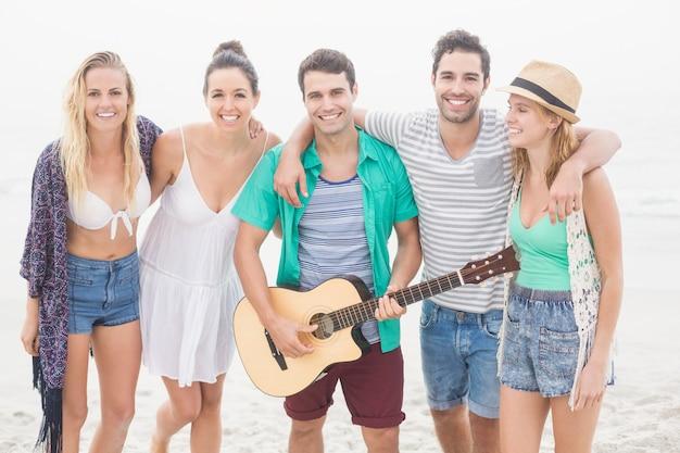 Grupo de amigos de pie en la playa con una guitarra