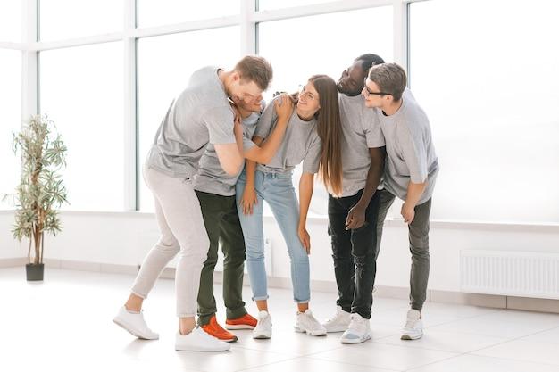 Grupo de amigos de pie en un salón espacioso y luminoso