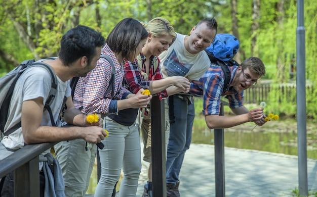 Grupo de amigos de pie sobre un pequeño puente en un parque en un día soleado