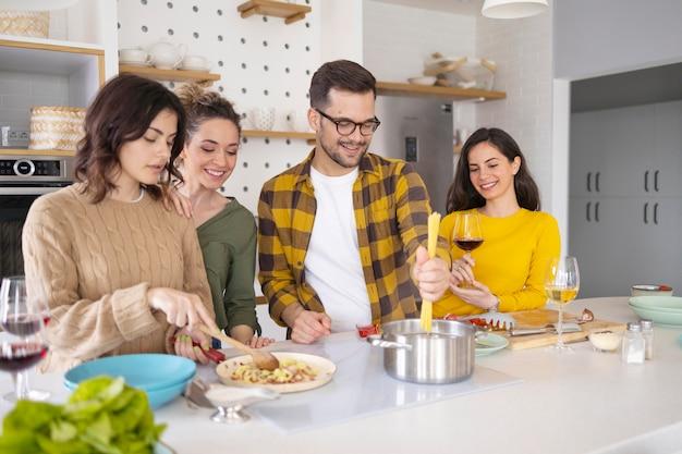 Grupo de amigos preparando comida en la cocina