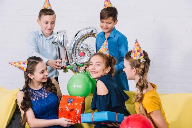 Grupo de amigos que celebran el cumpleaños dando regalos y sosteniendo una astilla número 16, globo de aluminio