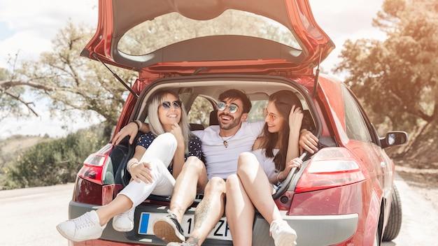 Grupo de amigos que disfrutan en el baúl del auto en la carretera
