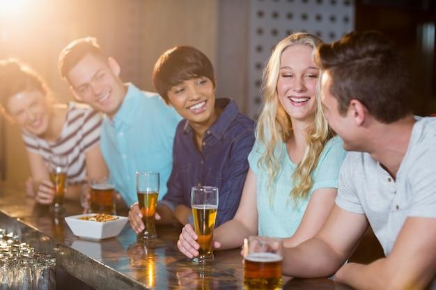 Grupo de amigos que interactúan entre sí mientras toman cerveza en la barra del bar