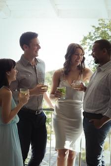 Grupo de amigos que interactúan entre sí mientras toman un cóctel