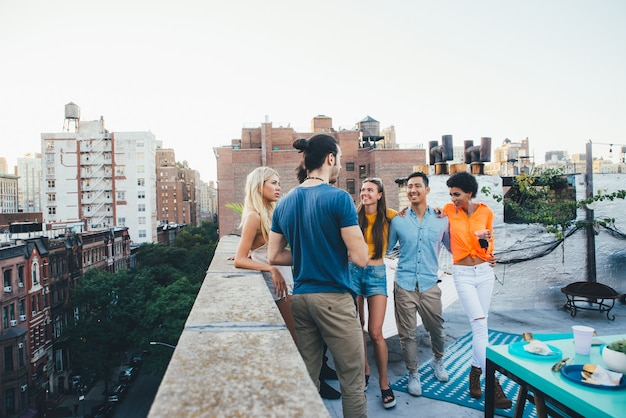 Grupo de amigos que pasan tiempo juntos en una azotea en la ciudad de nueva york, concepto de estilo de vida con gente feliz