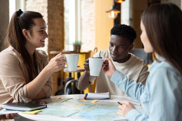 Grupo de amigos que planean un viaje en un café