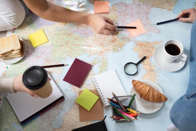 Grupo de amigos que planean un viaje mientras desayunan