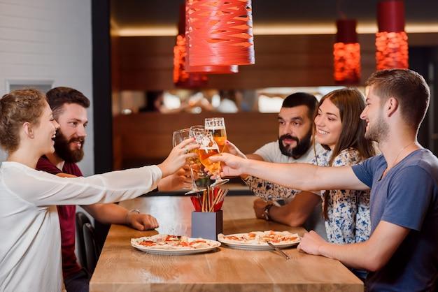 Grupo de amigos que tintinean vasos de cerveza en la pizzería.