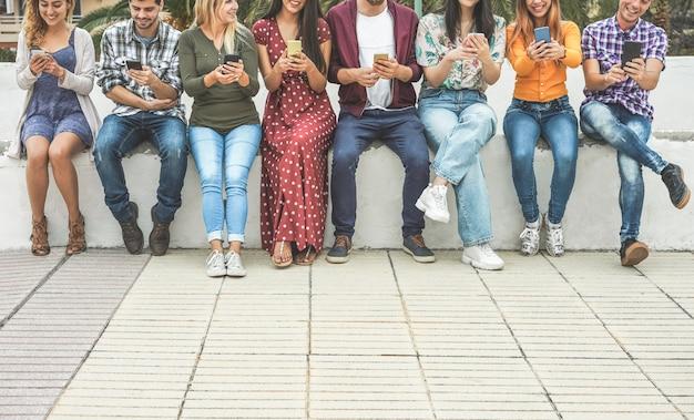 Grupo de amigos que usan la aplicación de teléfonos móviles inteligentes